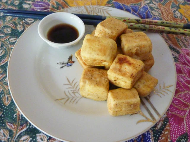 Salt and Pepper Tofu on a plate with dipping sauce and chopsticks