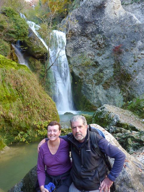 middle aged woman and older man posing in front of waterfall navarra, spain