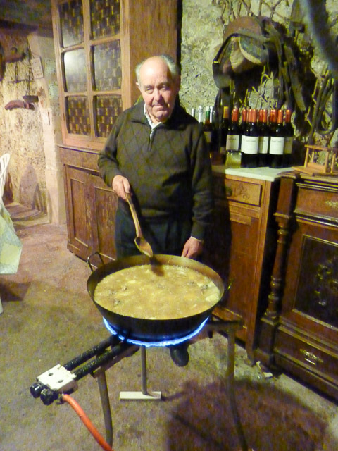 old man stand behind a wok with stew in it, stirring