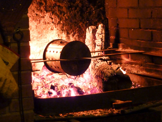 chestnuts roasting in a metal barrel over an open fire