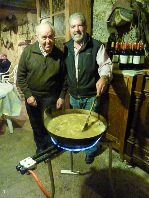 two older men stand in front of a wok with stew bubbling in it