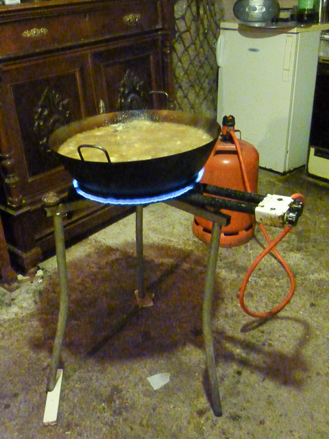 wok of stew on gas ring with gas bottle in background