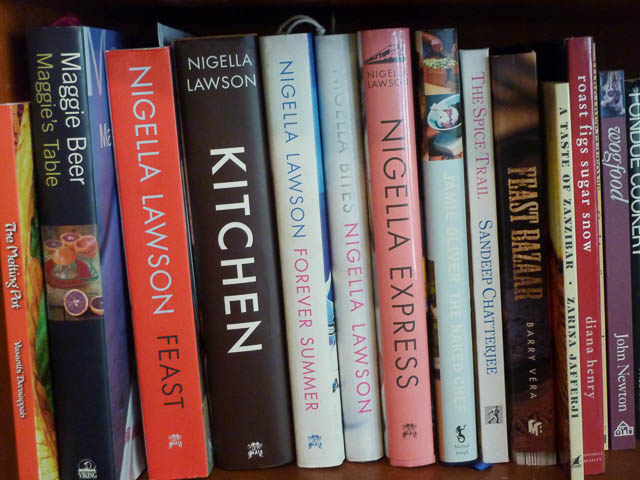 A row of cook books on a bookshelf