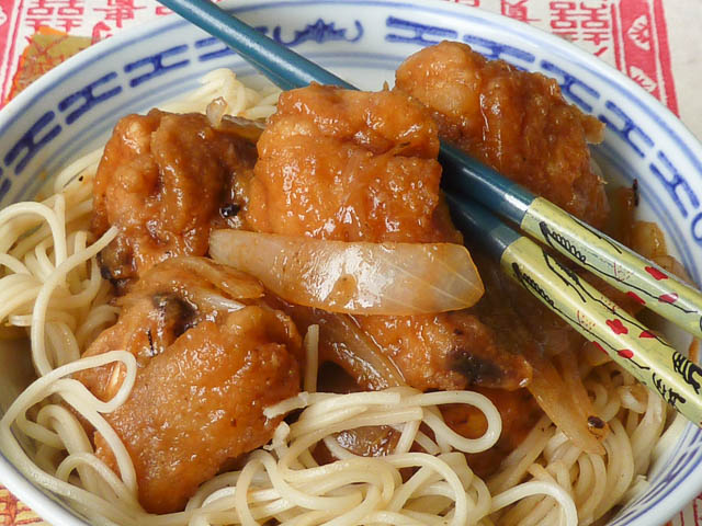 Chinese Garlic Ginger Chicken in a bowl with egg noodles and chopsticks