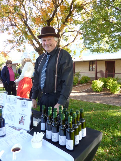 A Barossa local stand in front of a stall selling vincotto at the Vintage Festival Ziegenmarkt