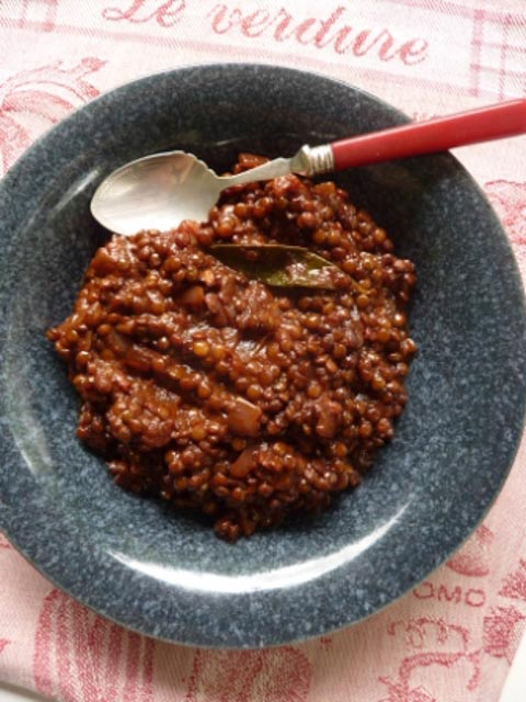 A dish of Richly Braised Lentils with a bay leaf and stewed, chopped onions in the bowl. A silver spoon with a red handle sit alongside the dish.