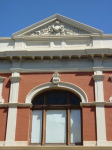 Historic Fremantle building in red brick and ochre paint - decorative arch 2