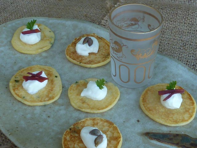 Small potato pancakes topped with sour cream and slivers of beetroot and capers