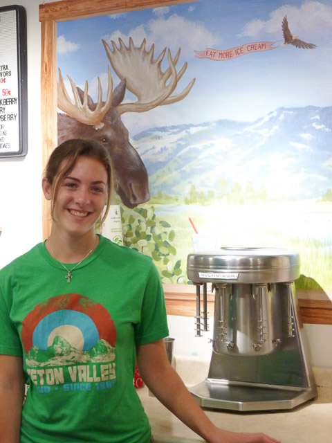Young girls in a t-shirt stand beside a milkshake mixer. She is in front of a painted sign of a moose and eagle saying 'eat more ice cream'. Full of hopes & dreams - Victor, Idaho USA