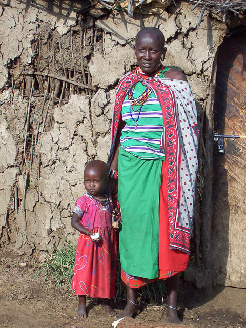 Mother & daughter in traditional Masai tribal outfits stand outside a bark hut - Masai Mara, Kenya