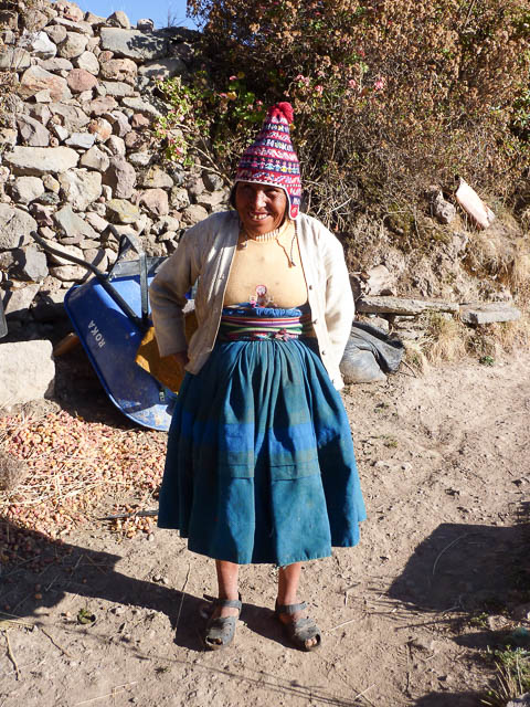 Woman in traditional Peruvian costume including full skirt and woolen beanie poses in her yard. - Amantini Island in the middle of Lake Titicaca, Bolivia