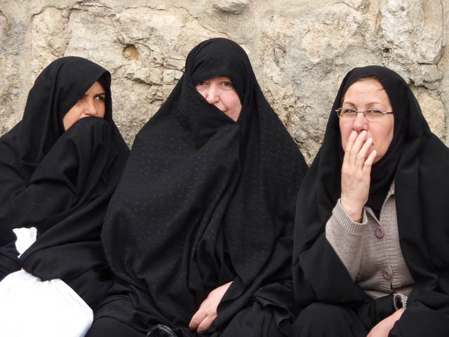 Three women in traditional Muslim carves and heavy robes cover their faces as they watch on with interest. - Damascus, Syria