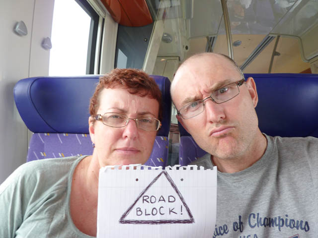 two people with frowning faces with a sign saying 'road block'