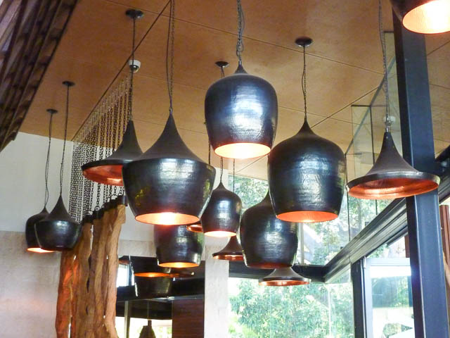 modern copper light fittings hanging in a group above a restaurant bar