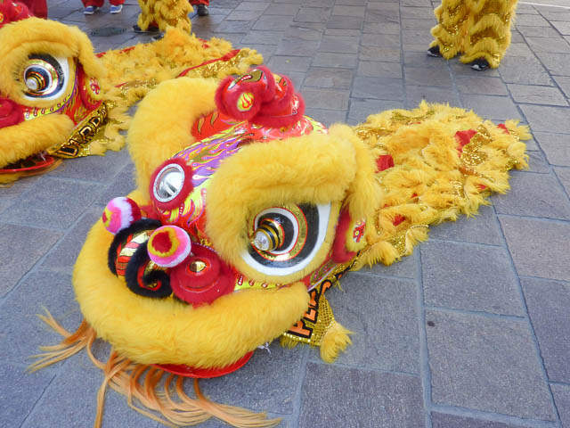 Bright yellow & red Chinese New Year Lion Dance Puppet resting on the ground.