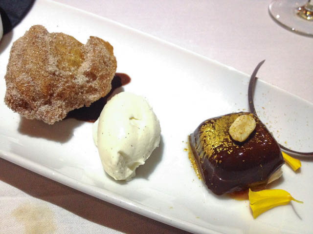 Dessert plate with churro, quenelle of cream and small chocolate bite topped with peanut and edible glitter