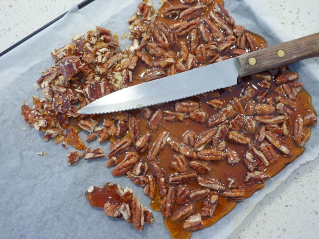 Pecan praline on a tray with a knife. Some of the praline is chopped small whilst the rest is in a solid sheet on the tray.