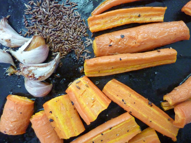 Ingredients for Carrot Dip with roasted carrots, garlic & cumin seeds on a baking tray