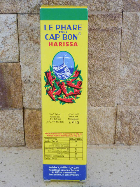 A tube of Le Phare du Cap Bon Harissa decorated withpictures of chillis and a lighthouse