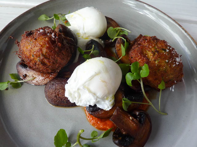 Breakfast plate of poached eggs, labneh, harissa sauce and pan fried mushrooms