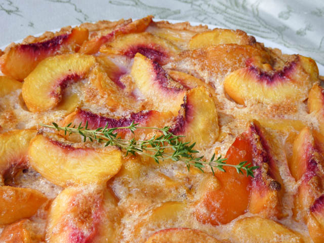 Closeup of Sliced Peachy Keen Tart decorated with thyme leaves