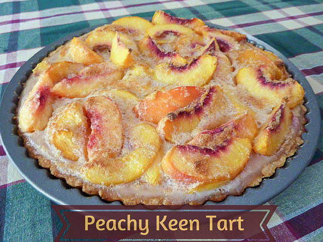 Sliced Peach Tart still in tart tin sitting on a chequered table cloth