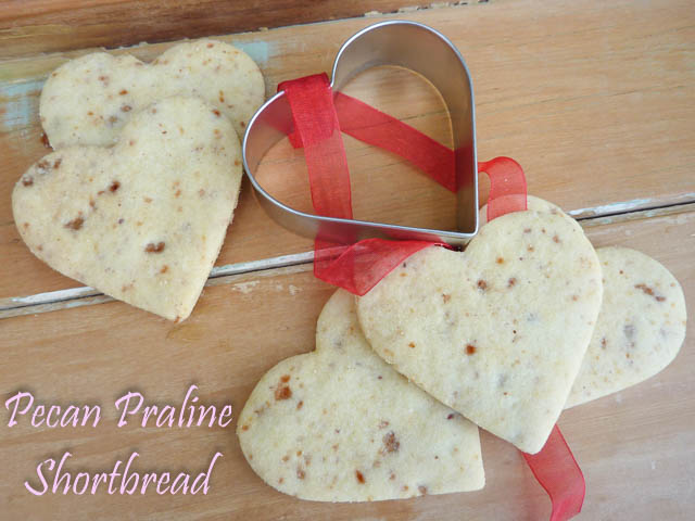 Pecan Praline Shortbread cut into heart shapes sit alongside the heart shaped biscuit cutter