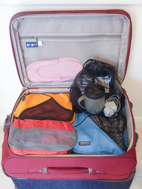 Open suitcase with packing cells and a drawstring bag inside - packing tips