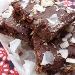 Squares of baked, chewy chocolate slice topped with coconut