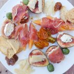 Plate of figs, cheese, prosciutto, olives and other antipasti ingredients