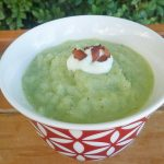 A bowl of chunky broccoli soup topped with sour cream and bacon
