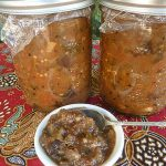 Two jars of eggplant kasundi (relish) with a small bowl of teh same relish with a spoon resting in it.