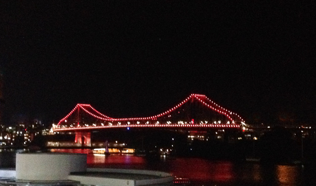 A night time view of Brisbane's Story Bridge, viewed from the CBD. The bridge is picked out in red lights.