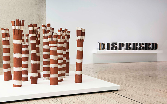 Wooden poles grouped together and painted decoratively with Aboriginal motifs; a modern artwork 'Dispersed' made of large wooden letters can be seen in the background. For NAIDOC week