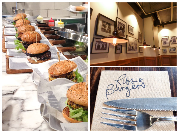 hamburgers lined up ready to be served; lighting in the restaurant; knife and fork resting on Ribs & Burgers serviette