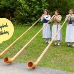 Three women in traditional folk dress play large musical horns in Ballenberg, Switzerland