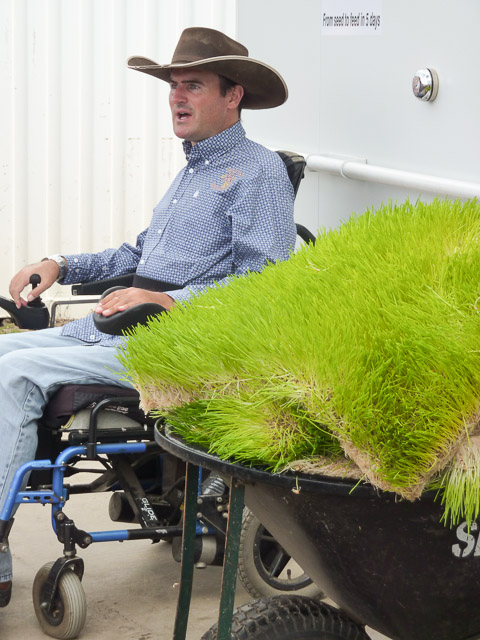 rob cook sits alongside a wheelbarrow of barley sprouts
