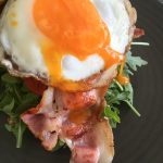 breakfast dish of bacon, aioli, rocket and tomato with a fried egg