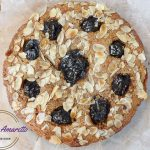 a whole prune and amaretto coffee cake with flaked almonds on top