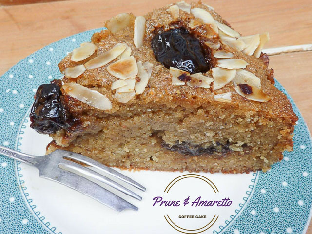 a wedge of prune almond cake with flaked almonds on top