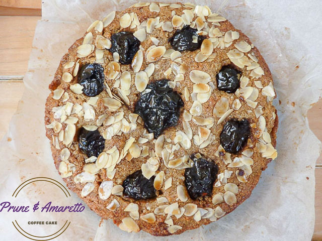a whole prune and almond coffee cake with flaked almonds on top