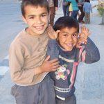 two boys clown around on the streets of palmyra, syria