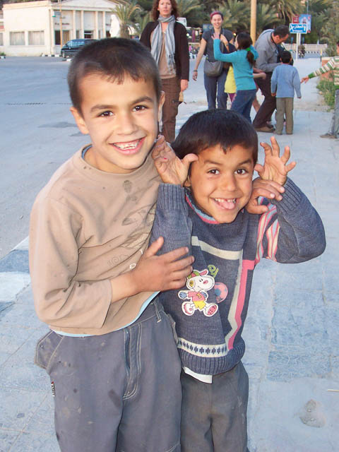 two boys clown around on the streets of palmyra, syria