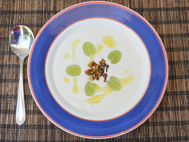 bowl of ajo blaco chilled spanish almond soup with garnishes