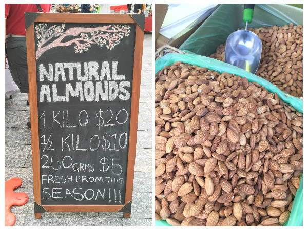 a pile of almonds and a sign selling them at the markets