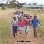Children full of excitement run down the path to greet visitors in Nakuru, Kenya