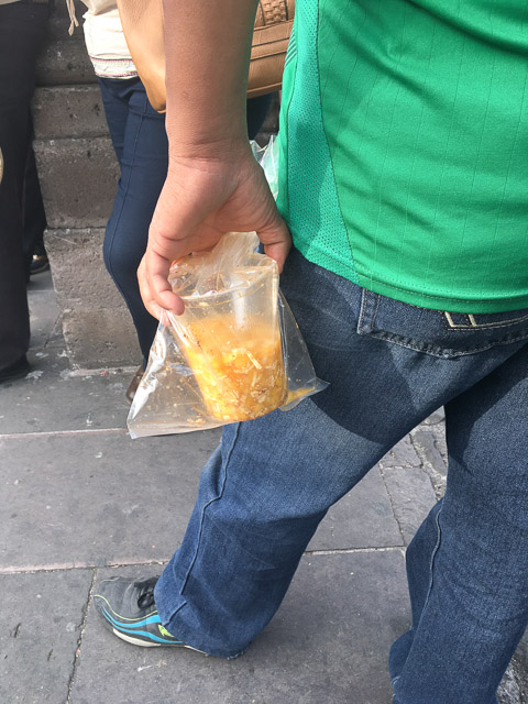 a local carries an unfinished cup of gaspachos morelianos