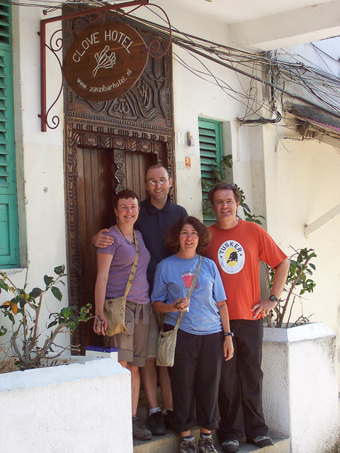 four people stand in front of the clove hotel in stone town, zanzibar