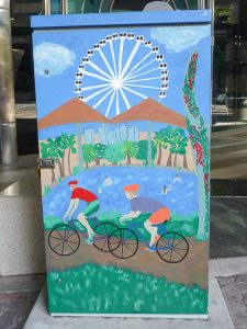 traffic signal box painted with two cyclists riding along a river, Brisbane