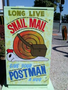 traffic signal box painted with snail carrying mail in a satchel on its shell
